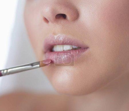 Photo pour Une photo d'une jeune femme, appliquer la poudre pour le visage dans la salle de bain. - image libre de droit