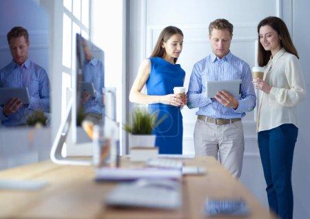 Photo pour Des gens d'affaires heureux utilisent une tablette numérique à l'extérieur d'un immeuble de bureaux. - image libre de droit