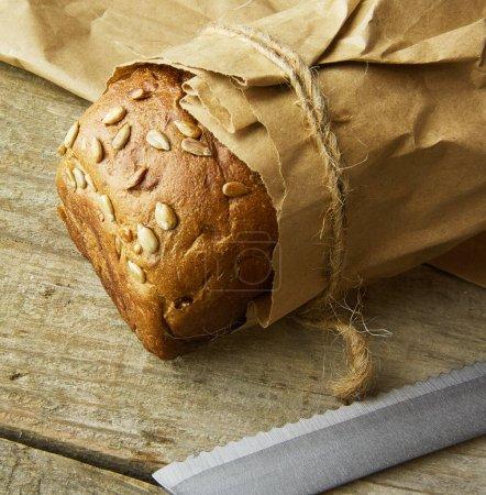 Photo pour Un pain emballé dans du papier sur une table en bois - image libre de droit