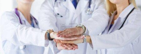 Photo pour Médecins et infirmières dans une équipe médicale empilant les mains. - image libre de droit