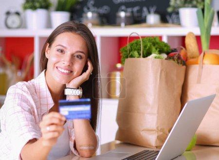 Photo pour Femme souriante, magasinage en ligne à l'aide de tablette et carte de crédit dans la cuisine. Femme souriante. - image libre de droit
