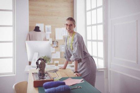 Photo pour Création de nouveaux styles à la mode. Jeune femme gaie cousant tout en s'asseyant à son lieu de travail dans l'atelier de mode. - image libre de droit