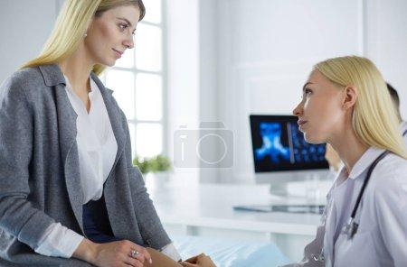 Photo pour Médecin et patient discuté d'un sujet tout en étant assis à la table. Concept de la médecine et des soins de santé. - image libre de droit