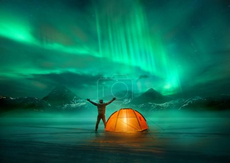Photo for A man camping in wild northern mountains with an illuminated tent viewing a spectacular green northern lights aurora display. Photo composition. - Royalty Free Image