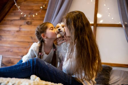 mom and daughter kiss their pet dog sitting on the bed in the bedroom