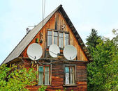 Antennas on a wall of the old wooden house