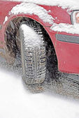 Wheel with  winter automobile tire in snowfall