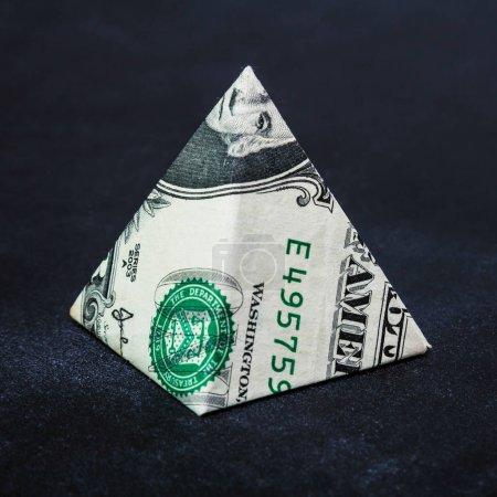 Photo pour Origami dollar pyramide argent symbole entreprise sur un fond noir - image libre de droit