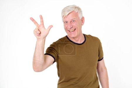 Photo pour Homme adulte avec les cheveux gris montre pouces chiffre trois debout isolé sur fond blanc. Signe gestuel à trois doigts . - image libre de droit