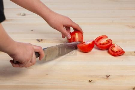 Cutting tomatoes for dishes on the table. Vegetabl...