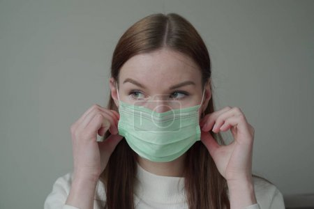 Photo for Close up of a beautiful young girl with long red hair in a medical mask. The girl looks towards the window. Orvi, coronovirus, influenza, acute respiratory infections - Royalty Free Image