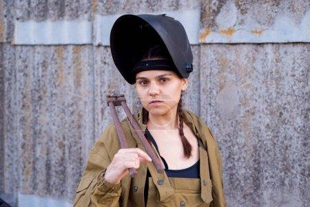 Photo pour Portrait d'une belle fille en uniforme, avec un casque de soudure et une grosse clé entre les mains. Le concept de femmes faisant un travail pénible et masculin - image libre de droit