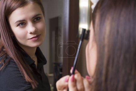 Photo pour Beauty saloon. Professional makeup artist Portrait of a young beautiful makeup artist girl. Makeup master does makeup to a girl. - image libre de droit