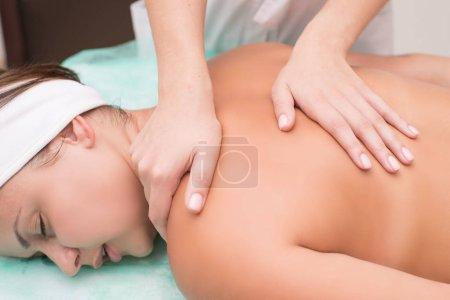 Photo pour Belle jeune femme relaxante avec massage des mains au spa masseur de beauté fait massage à une belle fille. Plaisir spa. Salon de beauté, massage du dos en gros plan. Massage relaxant du cou - image libre de droit