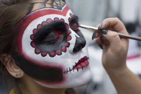 Photo pour Maquilleur professionnel fait du maquillage pour l'Halloween. Masque de fille mexicaine. Étapes de la demande dans un studio de maquillage. Un spécialiste en cosmétologie s'applique pour la Toussaint. Image mexicaine d'une fille dans un masque - image libre de droit