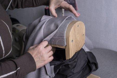 Photo pour Le processus de formation des épaules de la veste. Les mains du maître des vêtements, en utilisant le support de formage pour former les épaules de la veste, lissent les épaules de la veste en tissu. Étapes de confection de vêtements, confection d'un costume. Vêtements de repassage - image libre de droit