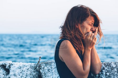 Young woman feeling sad by the sea