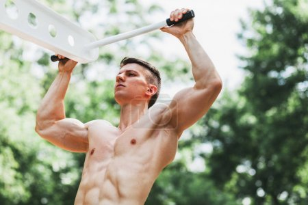 Muscular young man doing pull ups exercises on bar