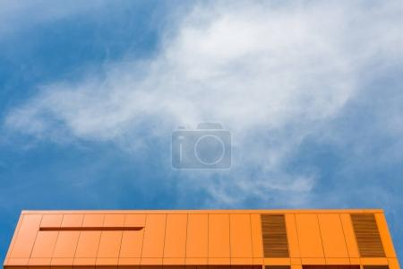 Top of orange building and blue sky
