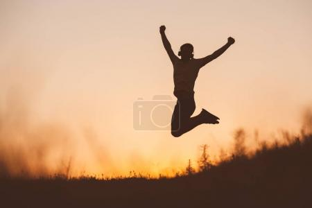 Silhouette of jumping man on sunset fiery sky background in mountain