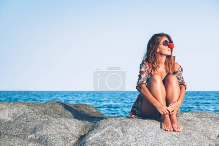 Photo for Young woman sitting on the rock enjoying sunbathing at the sea - Royalty Free Image