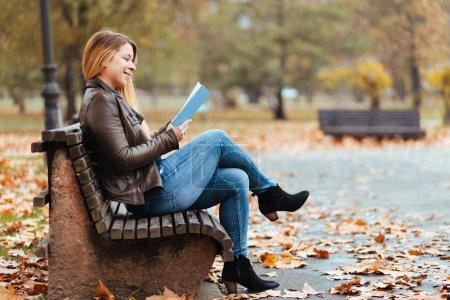 Photo pour Jeune femme qui aime lire un livre dans le parc en automne - image libre de droit