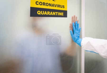Photo for A patient with covid-19 infection is quarantined in the negative room while a doctor gives treatemnts and support. coronavirus, medical, healthcare concept - Royalty Free Image