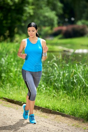 Photo for Attractive brunette woman running in outdoor park - Royalty Free Image