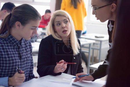 Photo pour Professeure d'architecture au travail. Une professeure explique les projets architecturaux aux étudiants. Belle professeure d'architecture universitaire souriant à la caméra. - image libre de droit