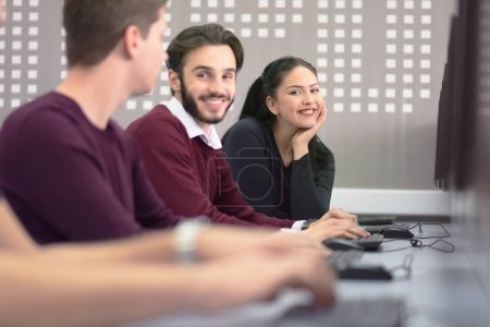 Photo pour Vue latérale des étudiants utilisant un ordinateur en laboratoire. Étudiant en informatique regardant et souriant dans la caméra pendant la classe à l'intérieur du laboratoire informatique. - image libre de droit