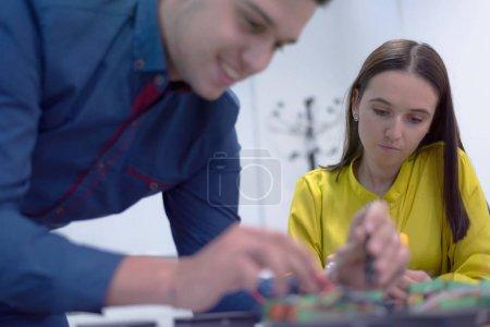 Photo pour Deux jeunes ingénieurs séduisants travaillant sur des composants électroniques.La technologie teste des équipements électroniques dans un centre de service. Centre de recherche scientifique technologiquement avancé. - image libre de droit