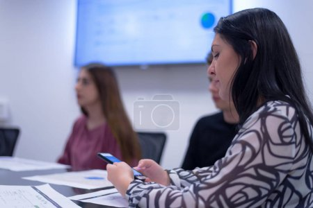 Photo for Young students listening the lecture with interest on university, female student using phone. - Royalty Free Image