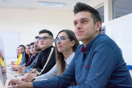 Photo for Group of muttiethnic IT students working at their computer lab.  Group of student listening lesson from their professor. Education and technology concept. - Royalty Free Image