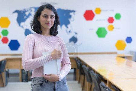 Photo pour Belle étudiante en informatique orientale regardant et souriant dans la caméra. - image libre de droit