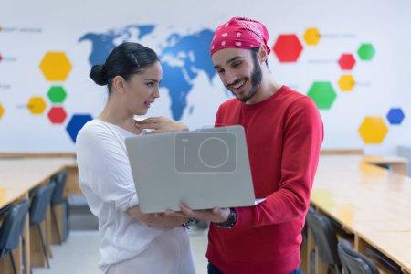 Photo pour Deux étudiants de collège multietchnic debout à l'intérieur de la salle de classe et en utilisant un ordinateur portable et la préparation pour leur classe. - image libre de droit