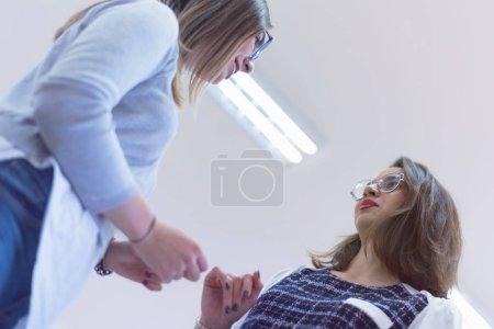Photo pour Deux étudiants se tenant à l'intérieur de la classe et bavardant après leur classe. Deux étudiants parlent et rient après la conférence. - image libre de droit