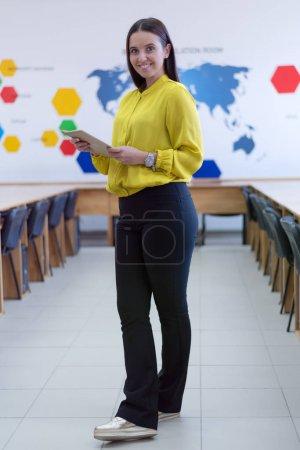 Photo pour Étudiante souriante debout dans la salle de classe et regardant la caméra. Hall universitaire intérieur. - image libre de droit