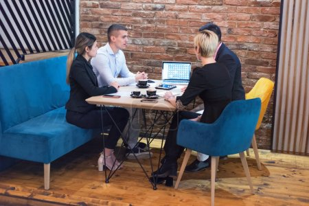 Photo for Group of a young business people brainstorming and discussing business plan on meeting at sunny bright office interior. - Royalty Free Image