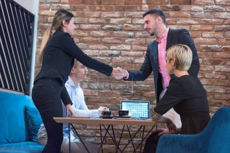 Photo for Business partners shake hands, standing in front of their office. Welcome to our team! Business people shaking hands while working in the creative office. - Royalty Free Image