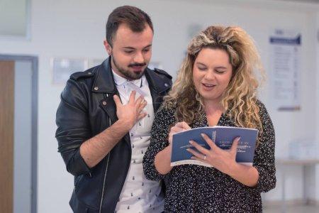 Photo pour Deux étudiants se tenant dans le couloir et bavardant après leur classe. Deux étudiants parlent et rient après la conférence - image libre de droit