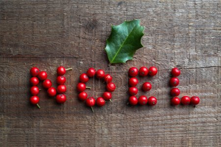 Photo for The word NOEL made from holly berries on wooden background - Royalty Free Image