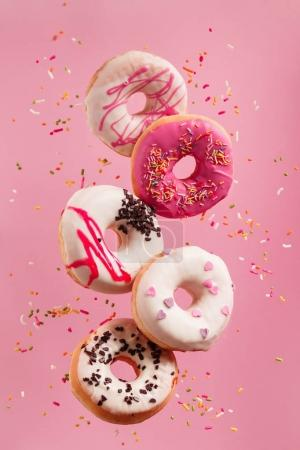 Photo for Various sweet donuts in motion falling on pink background - Royalty Free Image