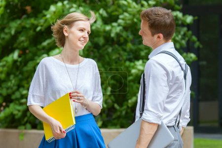 young colleagues is conversing on street