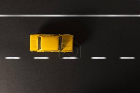 Photo pour Voiture jouet jaune sur fond noir avec des rayures sur la route . - image libre de droit