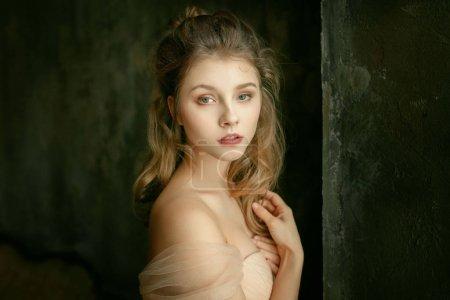 portrait d'une belle jeune fille dans un style historique dans un intérieur historique avec des fleurs