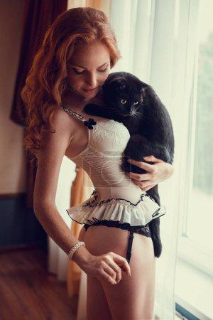 Photo pour Sexy femme souriante en soutien-gorge posant avec un chat noir à l'intérieur de la salle - image libre de droit