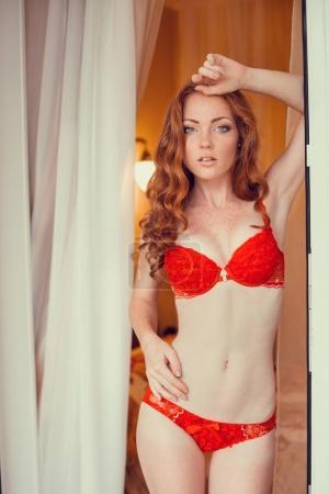 Photo pour Femme aux cheveux rouge souriante sexy en soutien-gorge rouge posant à l'intérieur de la salle - image libre de droit