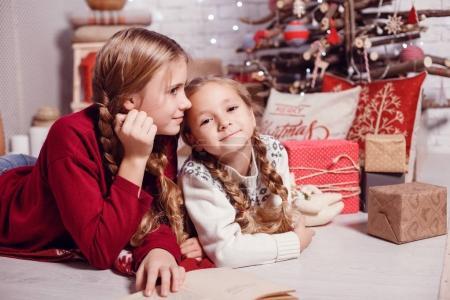 sisters posing near Christmas tree
