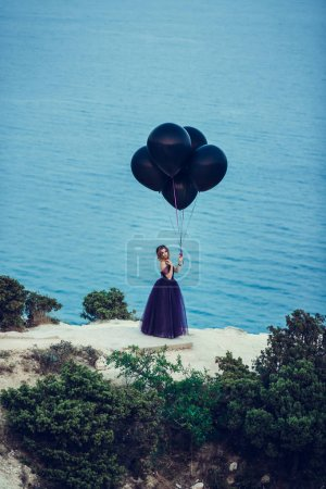 woman in dark dress holding balloons