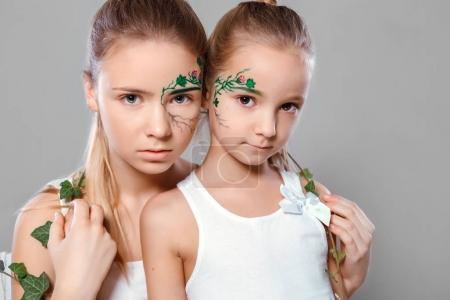 sisters with green paint on faces